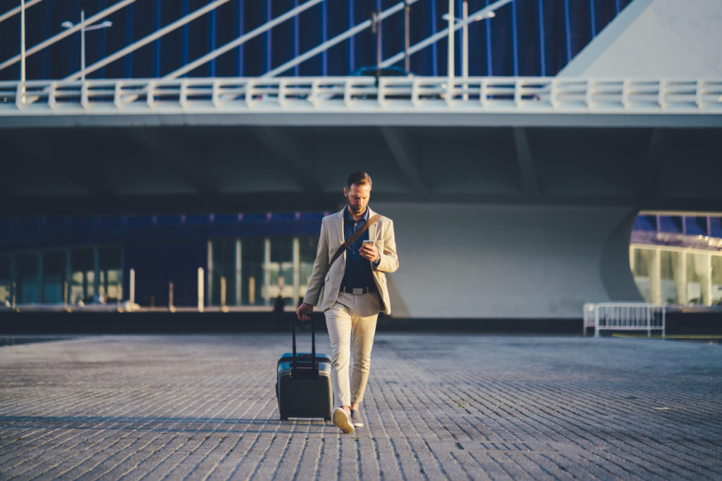 Man walking outside of airport checking his phone carrying luggage